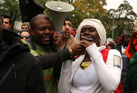 Eine Demonstrantin spricht in ein Megafon, das ein anderer Demonstrant ihr hinhält (Foto: Danny Frank)