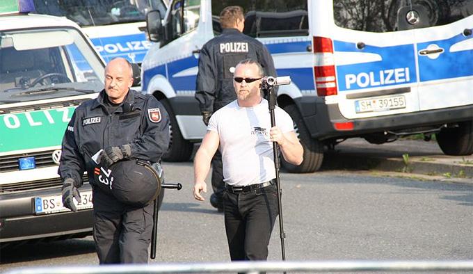 NPD-Funktionär Roy Elbert wird von der Polizei nach dem Vorzeigen eines Presseausweises zum Abfilmen der Gegendemo begleitet, Foto: Störungsmelder