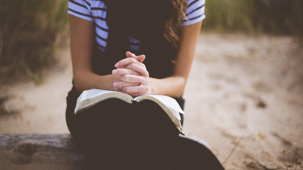 Mädchen sitzt, ihre gefalteten Hände auf einem Buch abgelegt. Ob sie betet oder nicht, bleibt der Vorstellung überlassen.