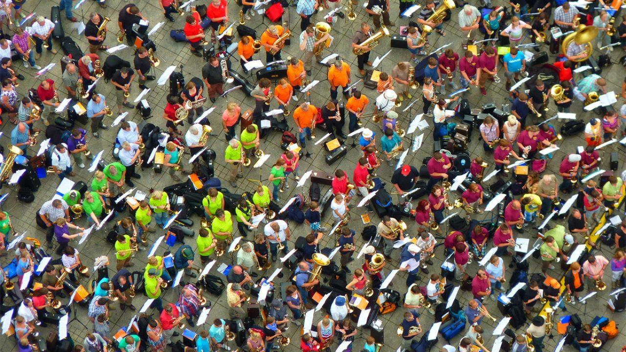 Ansammlung von Musiker*innen in bunten T-Shirts - Symbolbild für Vielfalt und Freiheit.
