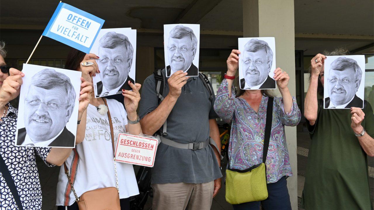 Demonstrierende halten sich Fotos des ermordeten Walter Lübcke vor das Gesicht.