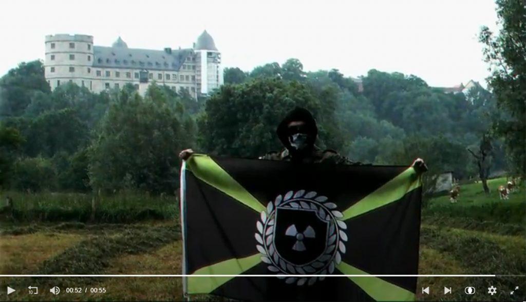 """Propaganda-Video von """"Atomwaffen Division"""": Mit Totenkopf-Maske vermummter Anhänger mit Flagge vor der Wewelsburg."""