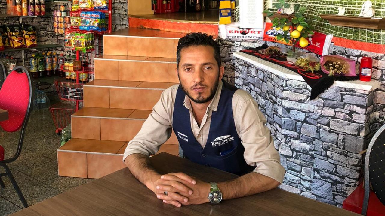 """İsmet Tekin, einer von 43 Nebenkläger*innen im Prozess gegen den Attentäter des Halle-Anschlags, sitzt in seinem Imbiss """"Kiez Döner""""."""