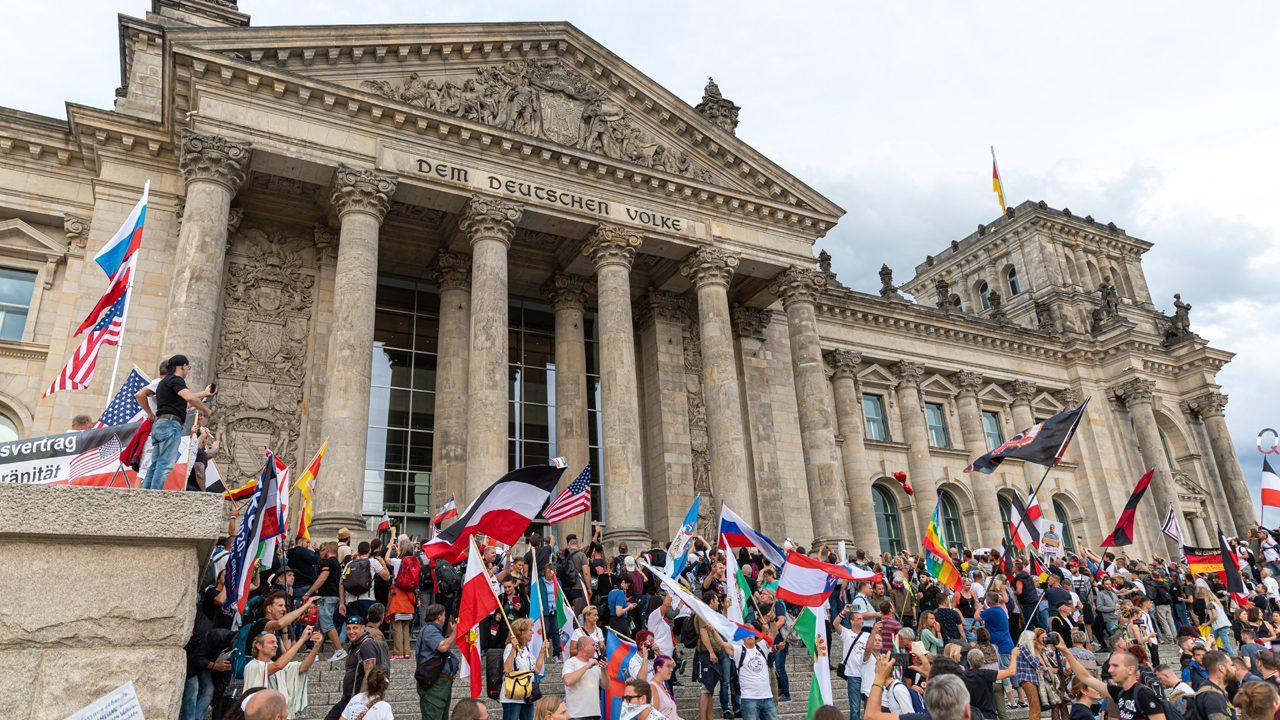 """Auf den Stufen des Reichstags: Zahlreiche Demoteilnehmer*innen wehen Reichsflaggen vor dem Parlamentsgebäude im Rahmen der """"Querdenken""""-Demo in Berlin."""