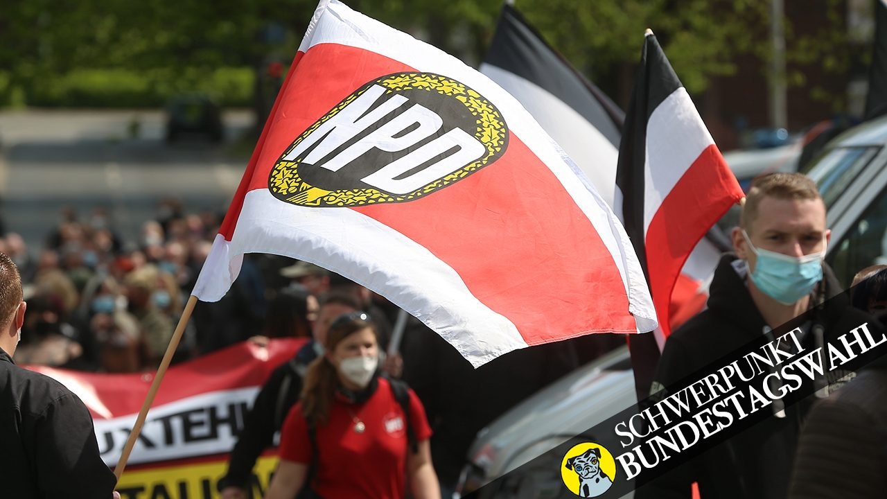 Anhänger:innen der NPD marschieren mit einer NPD-Fahne durch Essen im Mai 2021.