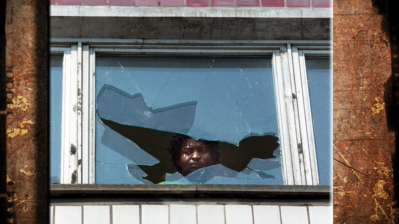 On 23 September 1991, an asylum seeker looks out a broken window at the residence for asylum applicants in Hoyerswerda in the German state of Saxony.